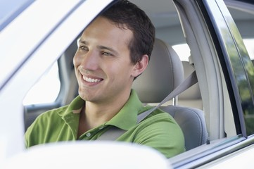 Smiling mid adult man driving a car