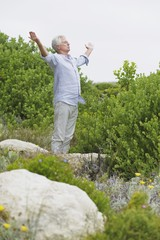 Senior man standing with his arm outstretched in a garden