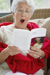 Senior woman reading a magazine and looking surprised