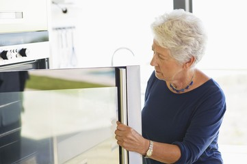 Senior woman looking into an oven