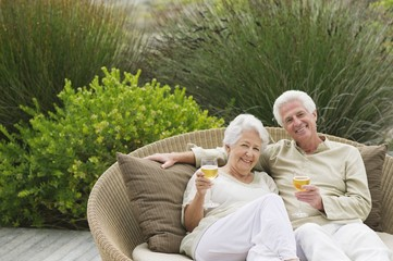 Senior couple sitting in a wicker couch holding wine glasses