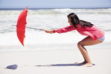 Woman trying to hold an umbrella in strong wind on the beach