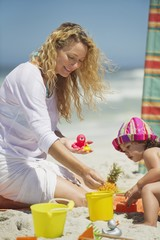 Woman with her daughter playing with pail and shovel on the beach