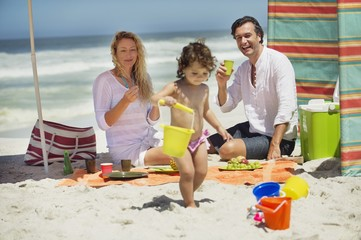 Girl playing on the beach with her parents sitting behind her