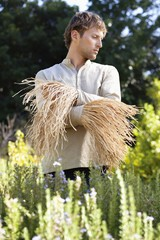 Young man standing in a field as scarecrow