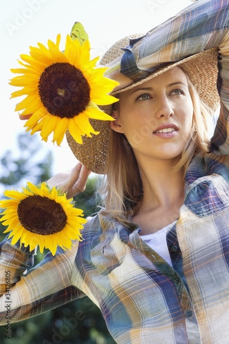 Young woman holding sunflowers