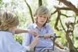 Children making frame of driftwood outdoors