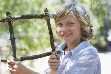 Portrait of a cute little boy holding frame of driftwood outdoors