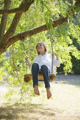 Happy little boy swinging on tree