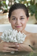 Portrait of a beautiful young woman holding bath sponge in a bathtub