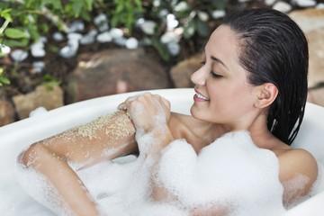 Beautiful young woman taking bubble bath