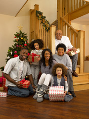 Mixed race family with Christmas tree and gifts