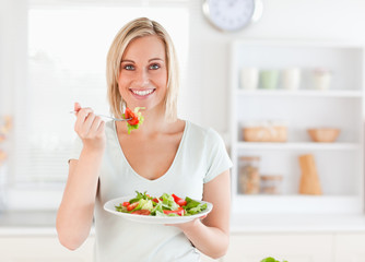 Close up of a gorgeous woman eating salad