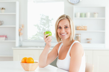 Young blonde woman holding a green apple smiling into the camera