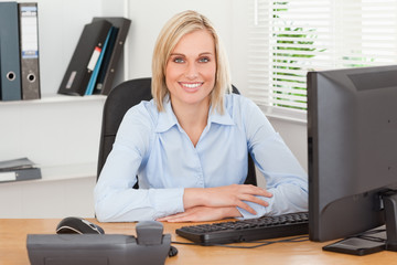Smiling woman sitting behind a desk