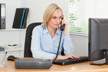 Smiling businesswoman on the phone looking at her screen