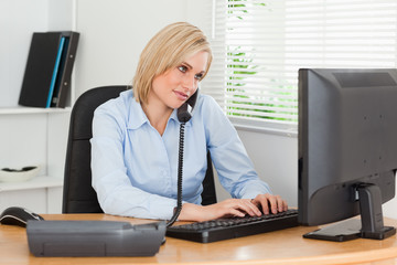 Working businesswoman on the phone while typing