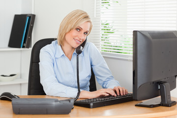 Working businesswoman on the phone while typing looks into camer