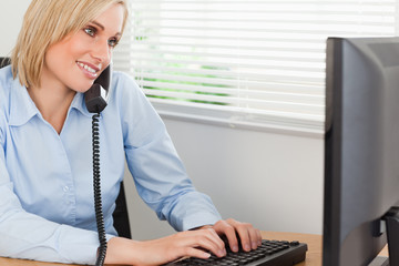 Smiling blonde businesswoman on the phone while typing looks at