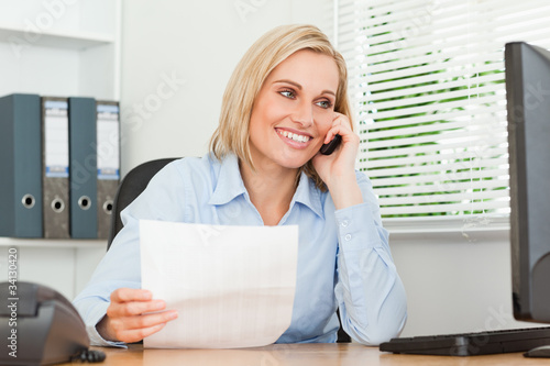 Portrait of a businesswoman looking up from a letter to her scre