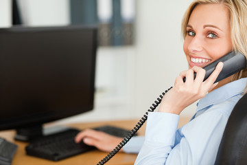 Young blonde businesswoman smiling into camera while on the phon