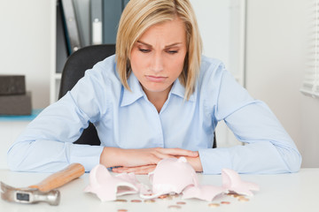 Sulking woman sitting in front of an shattered piggy bank with l