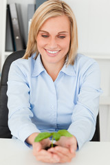 Businesswoman looking at little green plant
