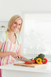 Gorgeous woman cutting red pepper looks into camera