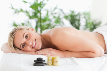 Smiling blonde woman lying on a lounger with stones and candles