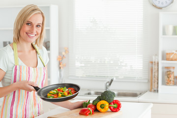 Woman showing cutted peppers in pan