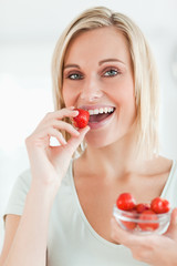 Portrait of a woman enjoying eating strawberries looking into th