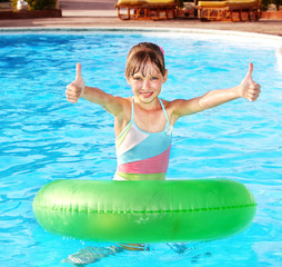 Child sitting on inflatable ring thumb up.