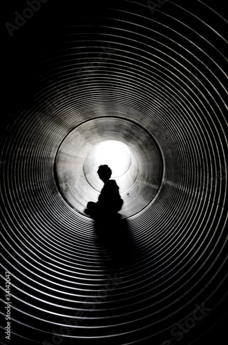 The silhouette of sitting boy with light at the end of tunnel