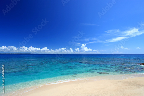 コマカ島の澄んだサンゴ礁の海と青い空