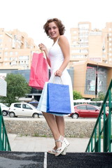 Girl in white dress holding a package with their purchases