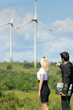 Green energy businesspeople in field show windmill