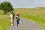 Hiking young couple backpack tramping asphalt road poster