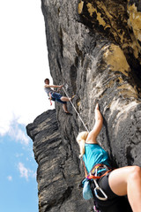 Rock climbing male instructor woman hang rope
