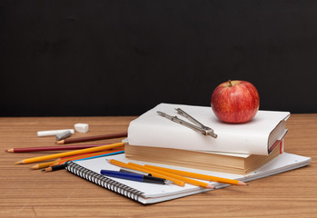 School Supplies with apple on black desk background