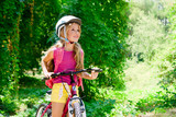 Fototapety Children girl riding bicycle outdoor in forest smiling