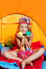 Children girl playing with balls inside camping tent