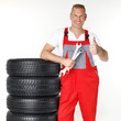 Motor mechanic next to a set of winter tyres shows thumb up