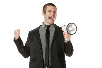 Portrait of a young business man yelling into a megaphone.