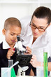 teacher helping schoolboy in science class