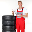 Motor mechanic next to a set of winter tyres holding a bottle