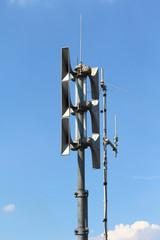 sirene auf hochhaus vor blauen himmel