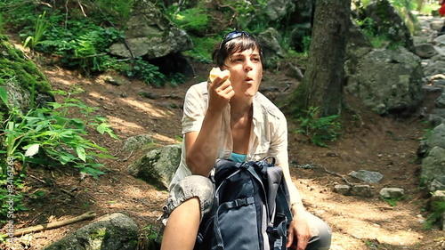 Female hiker resting and eating apple