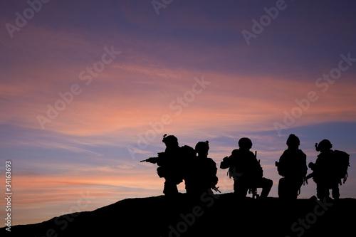 Leinwanddruck Bild Silhouette of modern troops in Middle East silhouette