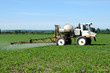 Close up side view of tractor spraying pesticides on crop