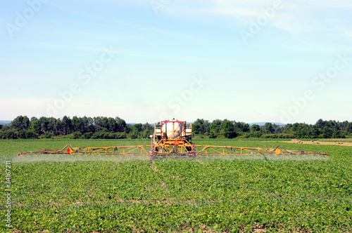 Full rear view of tractor spraying pesticides on crop